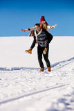 Couple playing in snow. Man giving woman piggyback ride on winter vacation. Stock Images