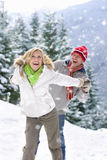 Couple playing in snow on ski slope Stock Image