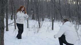 Couple playing snowballs in forest. Happy adult couple playing snowballs in winter forest together stock footage