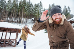 Couple playing snowballs in winter forest Stock Photography