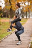 A couple playing sports in an autumn park. The guy crouches holding the girl on his shoulders. Outside. Stock Photography