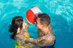 Couple playing in swimming pool Stock Photography