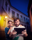 Couple playing with tablet on the street Stock Photos