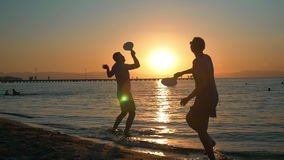 Couple playing tennis on the beach at sunset. Slow motion of young man and woman playing tennis by the sea at sunset. Golden sun reflecting in dark water. Active stock video