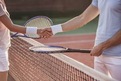 Couple playing tennis. Cropped image of men and women shaking their hands while playing tennis on tennis court outdoors Stock Photo