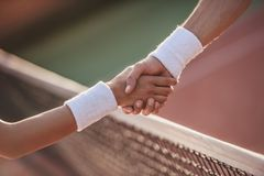 Couple playing tennis. Cropped image of men and women shaking their hands while playing tennis on tennis court outdoors Stock Images