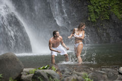 Couple Playing Under Waterfalls Royalty Free Stock Photos