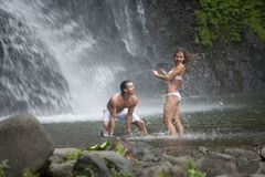 Couple Playing Under Waterfalls royalty free stock images