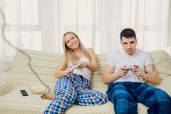Couple playing video game sitting on sofa in room. Couple playing video game sitting on sofa in room on window background Stock Photo
