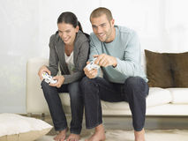 Couple Playing Video Game On Sofa Royalty Free Stock Image