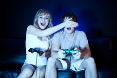 Couple playing video games. A shot of a young couple playing video games in the living room Royalty Free Stock Photography