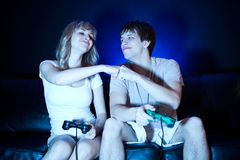 Couple playing video games. A shot of a young couple playing video games in the living room Stock Photos