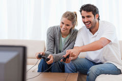 Couple playing video games. In their living room Royalty Free Stock Photos