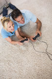Couple playing video games on area rug. High angle view of a couple playing video games on area rug at home Stock Photography