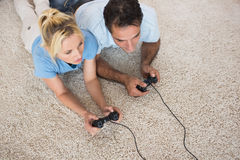 Couple playing video games on area rug at home Stock Image