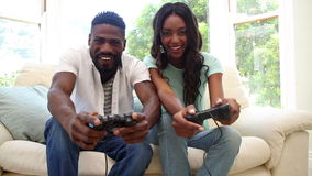 Couple playing video games on the couch stock footage