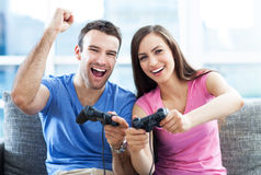 Couple playing video games. Excited couple playing video games on the sofa Stock Photography