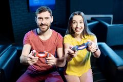 Couple playing video games with gaming console in the club stock image