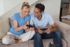 Couple playing video games in living room Stock Photography