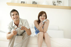 Couple Playing Video Games on Sofa Royalty Free Stock Photo