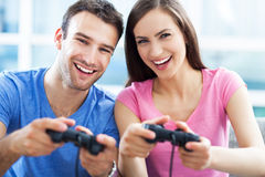 Couple playing video games. On the sofa Stock Photos