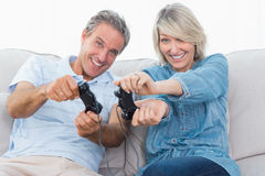Couple playing video games on the sofa. At home in living room Royalty Free Stock Photo