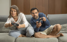 Couple playing video games in their city apartment. Middle aged couple playing video games in their city apartment Royalty Free Stock Photo