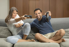 Couple playing video games in their city apartment. Middle aged couple playing video games in their city apartment Royalty Free Stock Images