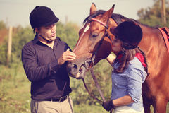 Free Couple Playing With A Horse Stock Photo - 57858880