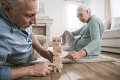 Couple playing wood blocks game at home Royalty Free Stock Image