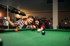 Couple plays in billiard room, male player aiming. Family couple plays in billiard room. Man and women leisures, american pool game, poolroom on background, male royalty free stock image