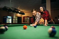 Couple plays in billiard room, male player aiming. Family couple plays in billiard room. Man and women leisures, american pool game, poolroom on background, male stock photography
