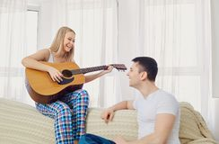 The couple plays the guitar, sings the songs together. The couple plays the guitar, sings the songs together in the room stock photos