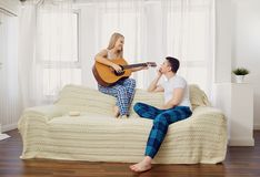 The couple plays the guitar, sings the songs together. The couple plays the guitar, sings the songs together in the room royalty free stock photo