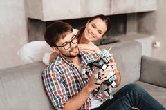 The couple plays with the robot a rhinoceros. The guy sits on the couch and holds the robot in his hands. The girl is standing behind him. She hugs the guy and stock photos