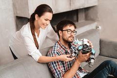 The couple plays with the robot a rhinoceros. The guy sits on the couch and holds the robot in his hands. The girl is standing behind him. She hugs the guy and royalty free stock images