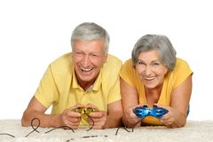 Couple plays video game. Mature couple plays video game at home on a white background royalty free stock image