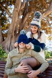 A couple plays with a woolen hat in a public park stock photography