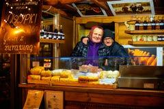 Couple plus âgé mignon qui fait le fromage fumé traditionnel Oscypek Image libre de droits