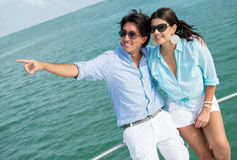 Couple pointing away in a yacht Stock Photos