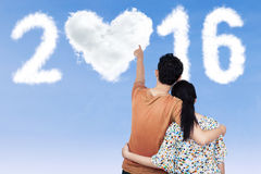 Couple pointing at clouds shaped numbers 2016 Royalty Free Stock Photos