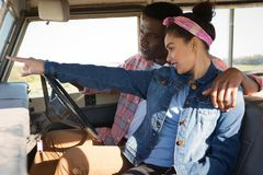 Couple pointing at distance while driving a car. At countryside Stock Photos