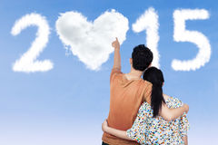 Couple pointing at heart shaped cloud Stock Image