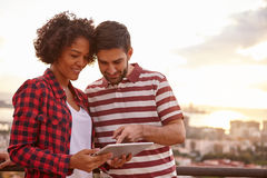 Couple pointing and looking at tablet. Young couple looking at tablet while he points at something on it while the sun is setting behind them over a city scape Stock Photo