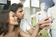Couple Pointing at Shop Window Royalty Free Stock Photography