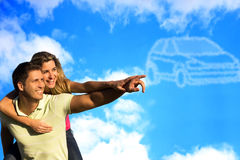 Couple pointing to clouds shaped like a car. Happy couple dreaming of a car and pointing to car shaped clouds Stock Photo