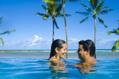 Couple in the pool. Happy Couple in love smiling in the pool Stock Photography