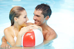Couple in pool with beach ball Royalty Free Stock Photo