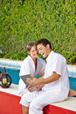 Couple at pool with tablet PC Stock Photos