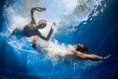 Couple in the pool. Underwater shot of couple jumping in the pool Royalty Free Stock Images